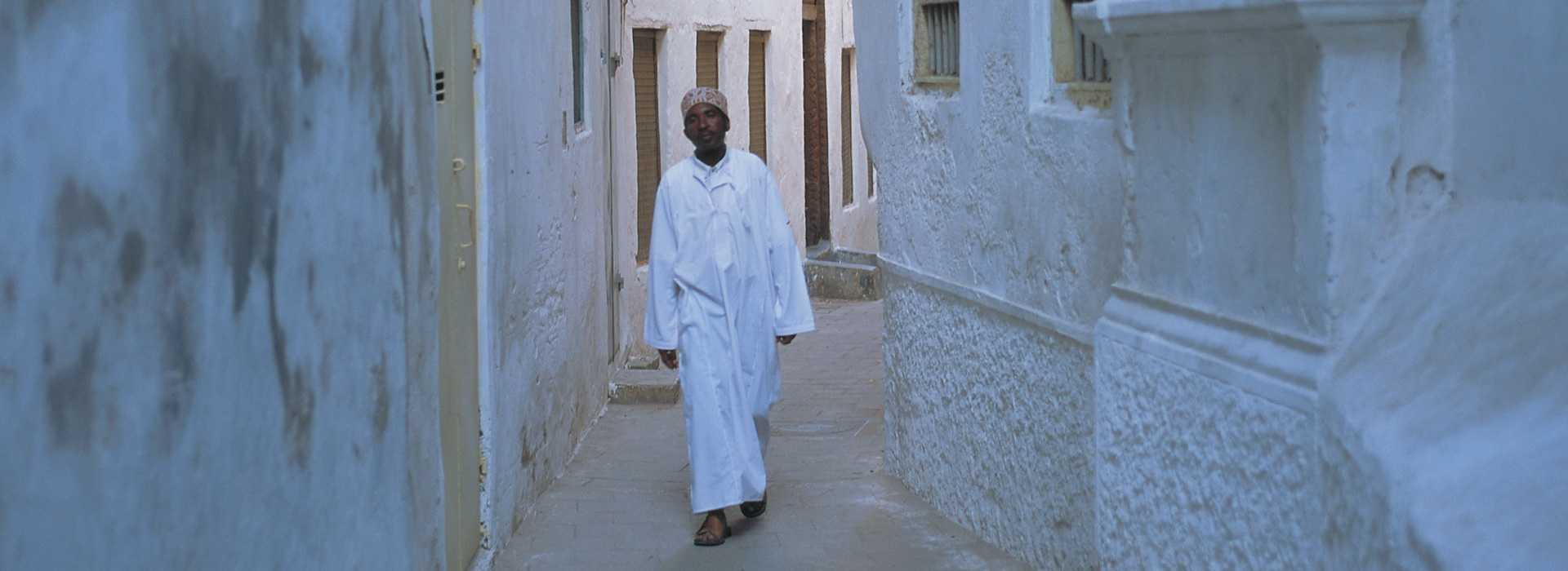 Man Walking Through The Streets Of Stone Town