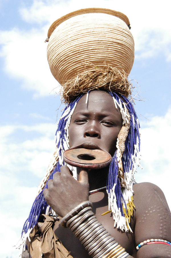 Mursi Woman with a lip plate and basket on her head in Ethiopia