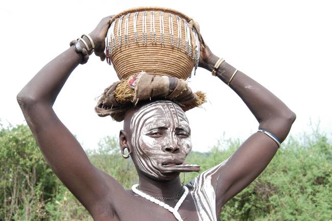 Mursi Tribeswoman carrying basket on head, Ethiopia