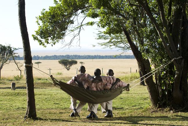 Three staff members relax in a hammock overlooking the savannah