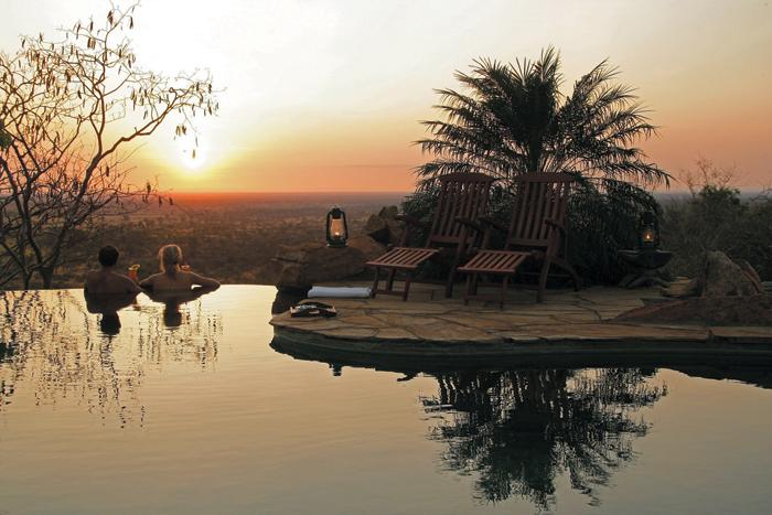 Couple in pool at sunset at Elsa's Kopje in Kenya