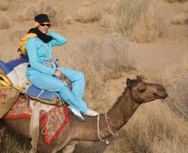 A WOMAN rides a CAMEL in the THAR DESERT during a SAFARI near JAISALMER - RAJASTHAN,