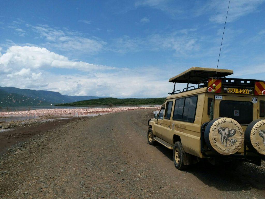 A Somak safari vehicle beside a lake full of flamingoes