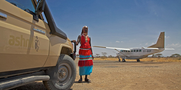 Masai warrior beside a Somak safari vehicle